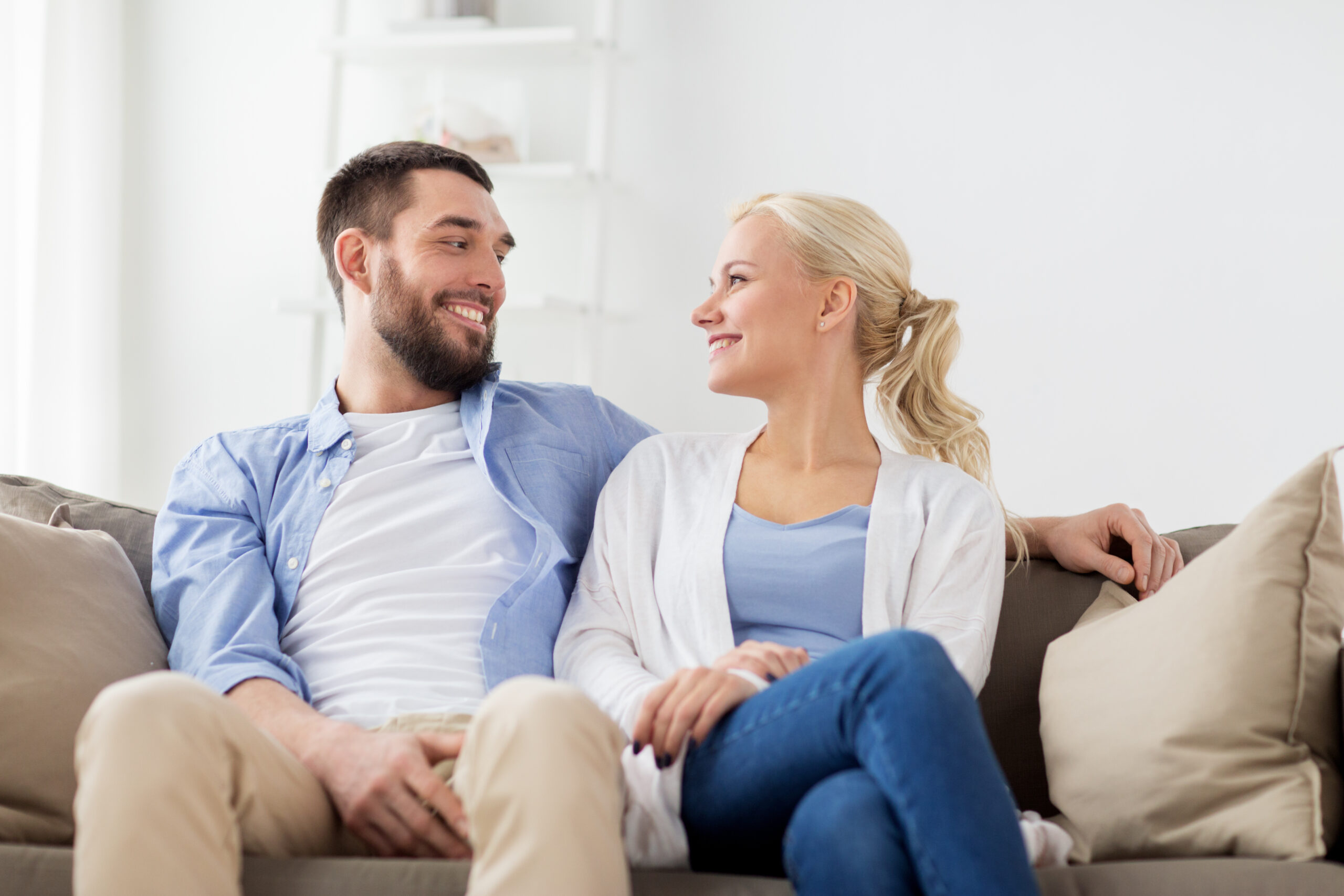 love, family and people concept - smiling happy couple sitting on sofa at home